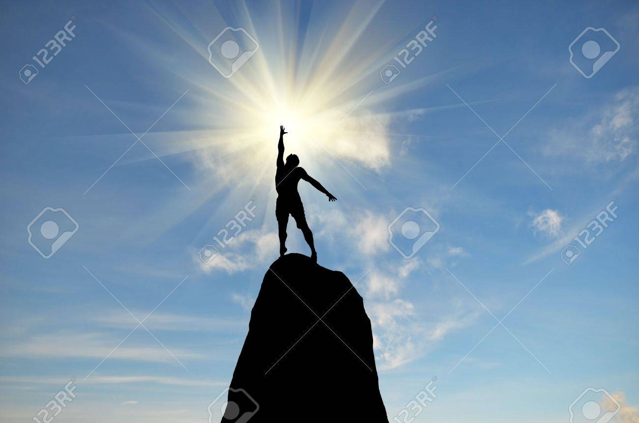 man on top of the mountain reaches for the sun Stock Photo - 12656102