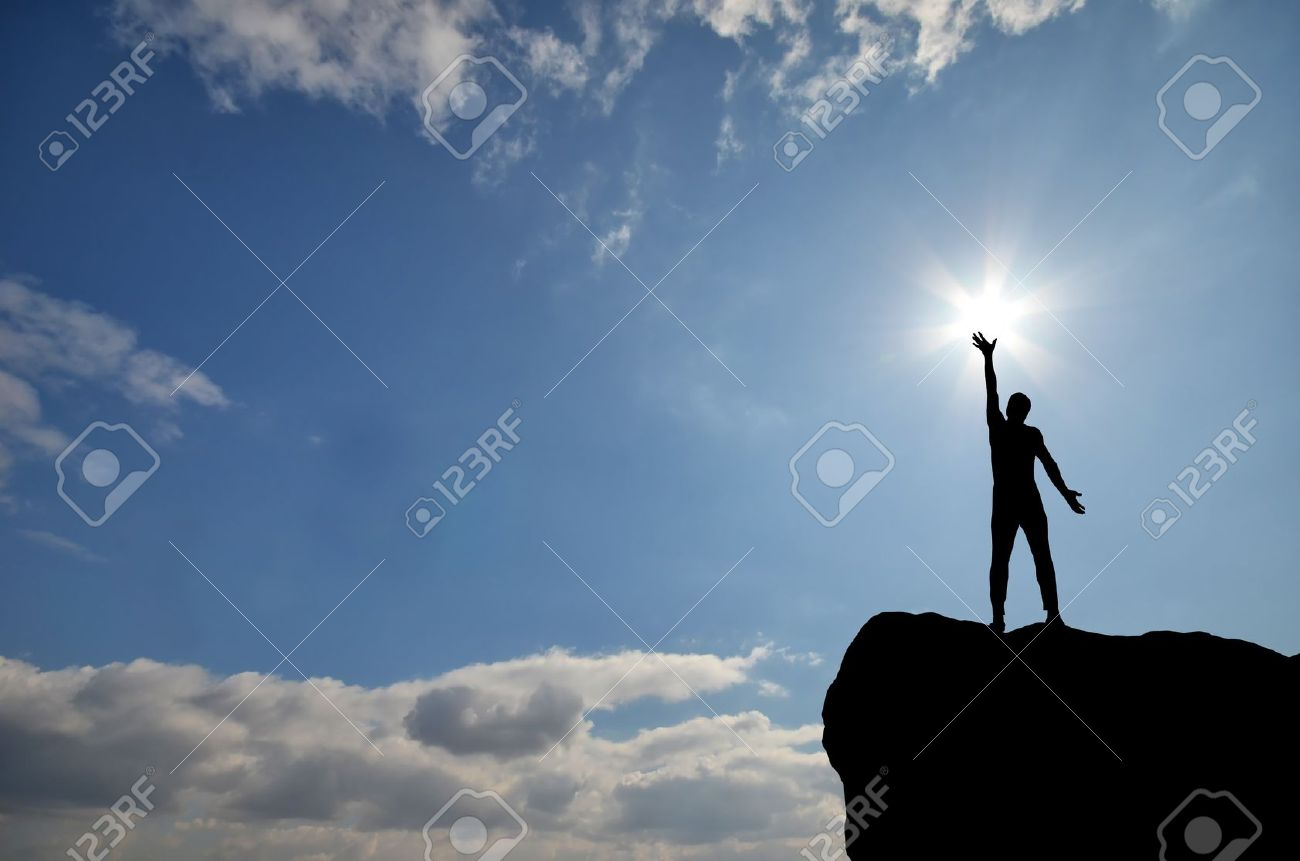 man on top of the mountain reaches for the sun - 12907733