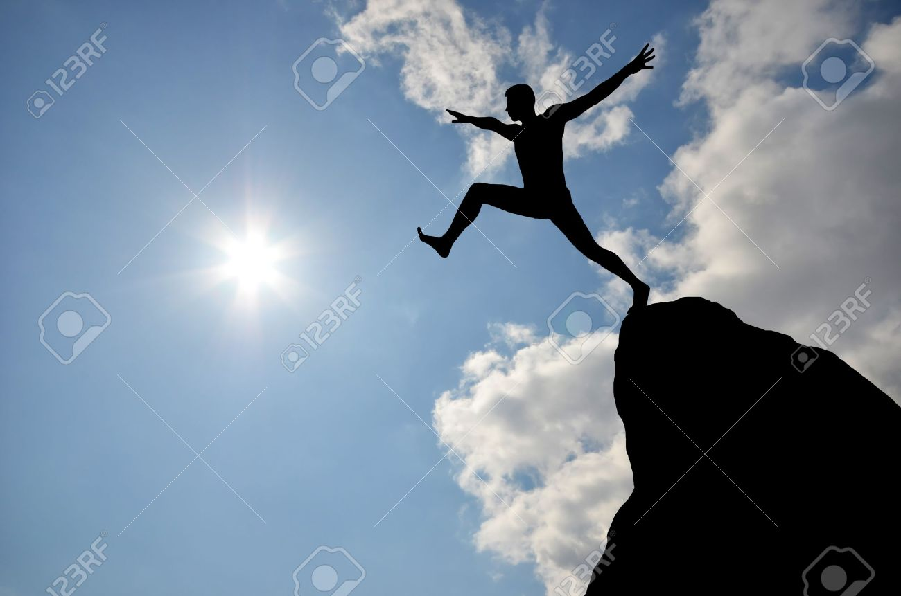 silhouette of a man jumping off a cliff in the direction of the bright sun - 12984398