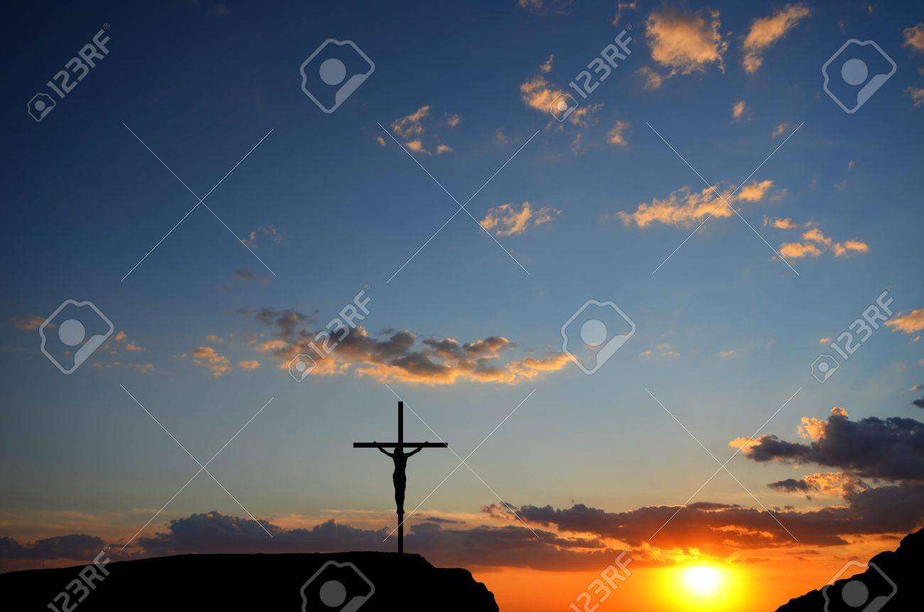 Crucifixion of Jesus Christ on the cross on a background sunset - 14396942