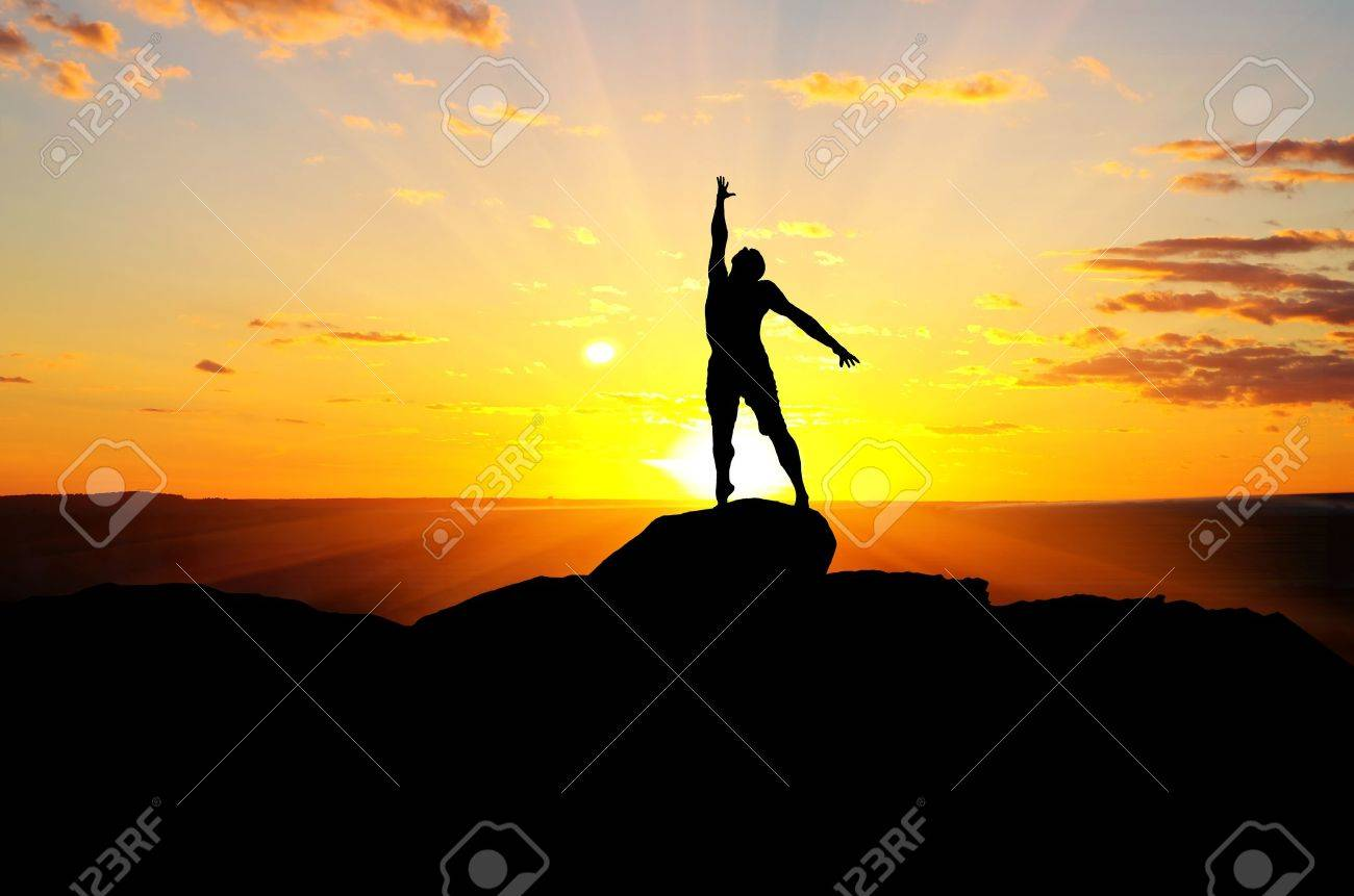 man on top of the mountain reaches for the sun - 16294408