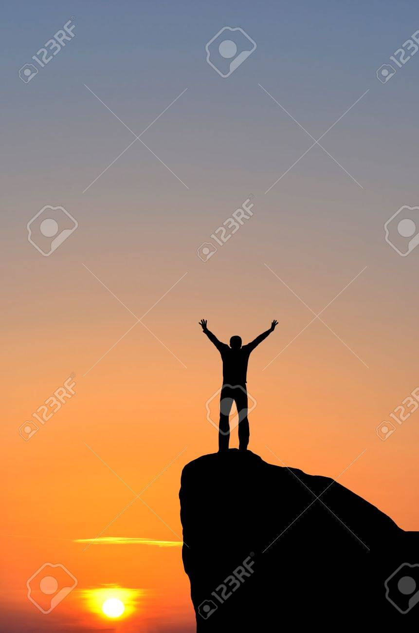 man on top of the mountain reaches for the sun - 16654606