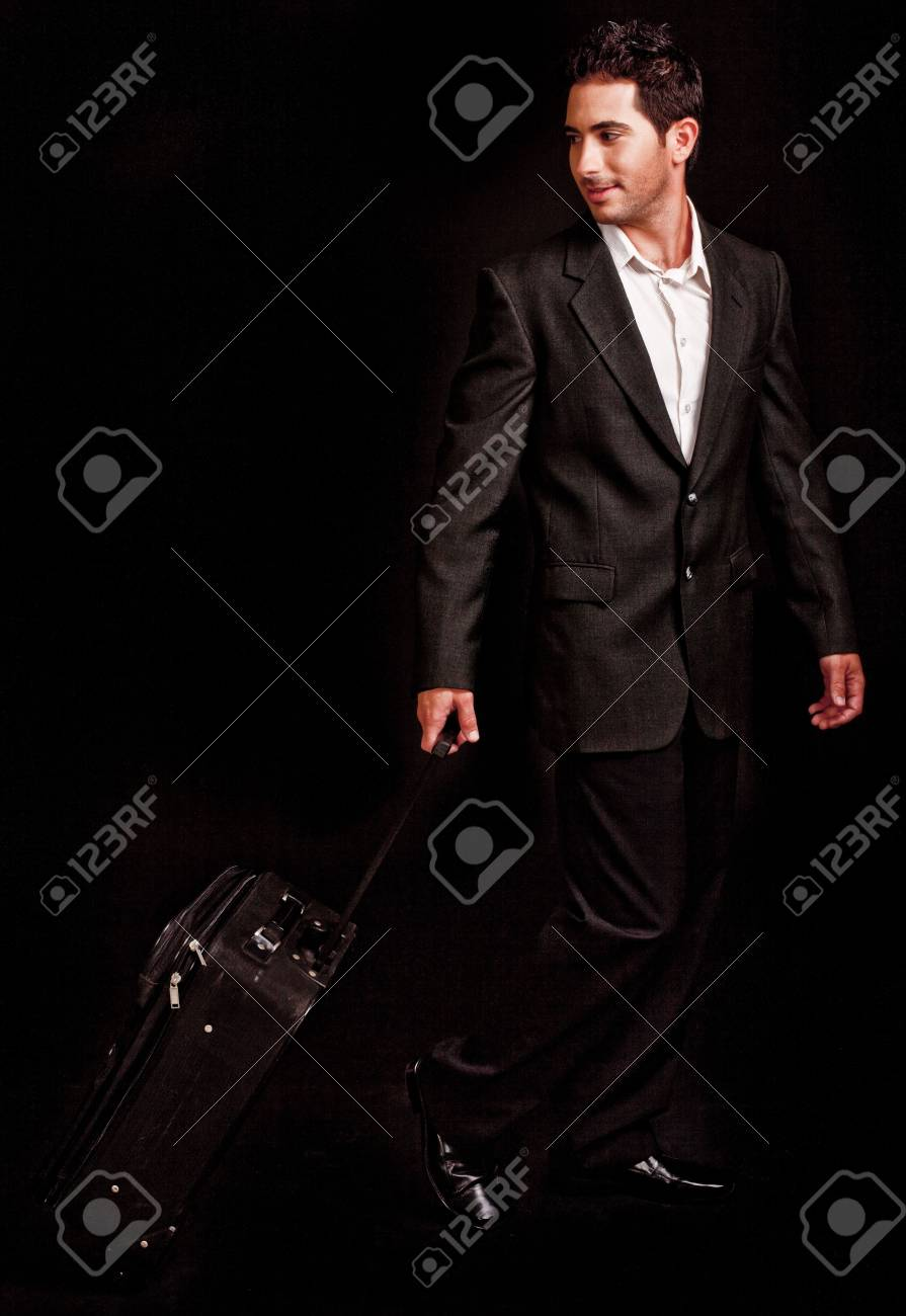 Business man pulling his luggage on black isolated background Stock Photo - 6085845