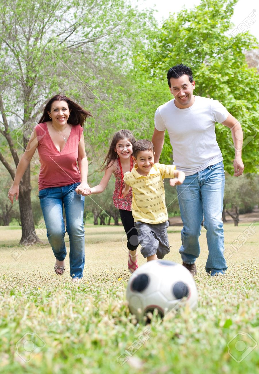 Parents and two young children playing soccer in the green field, outdoor Stock Photo - 7562271