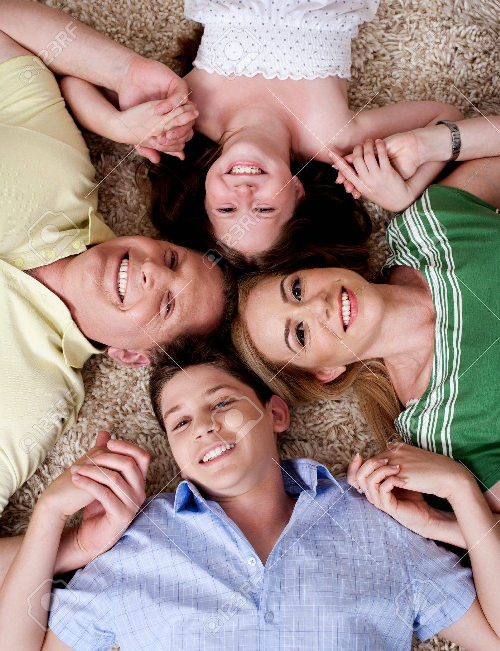 Happy family of four lying on the carpet and holding each others hand, looking at camera Stock Photo - 7673581