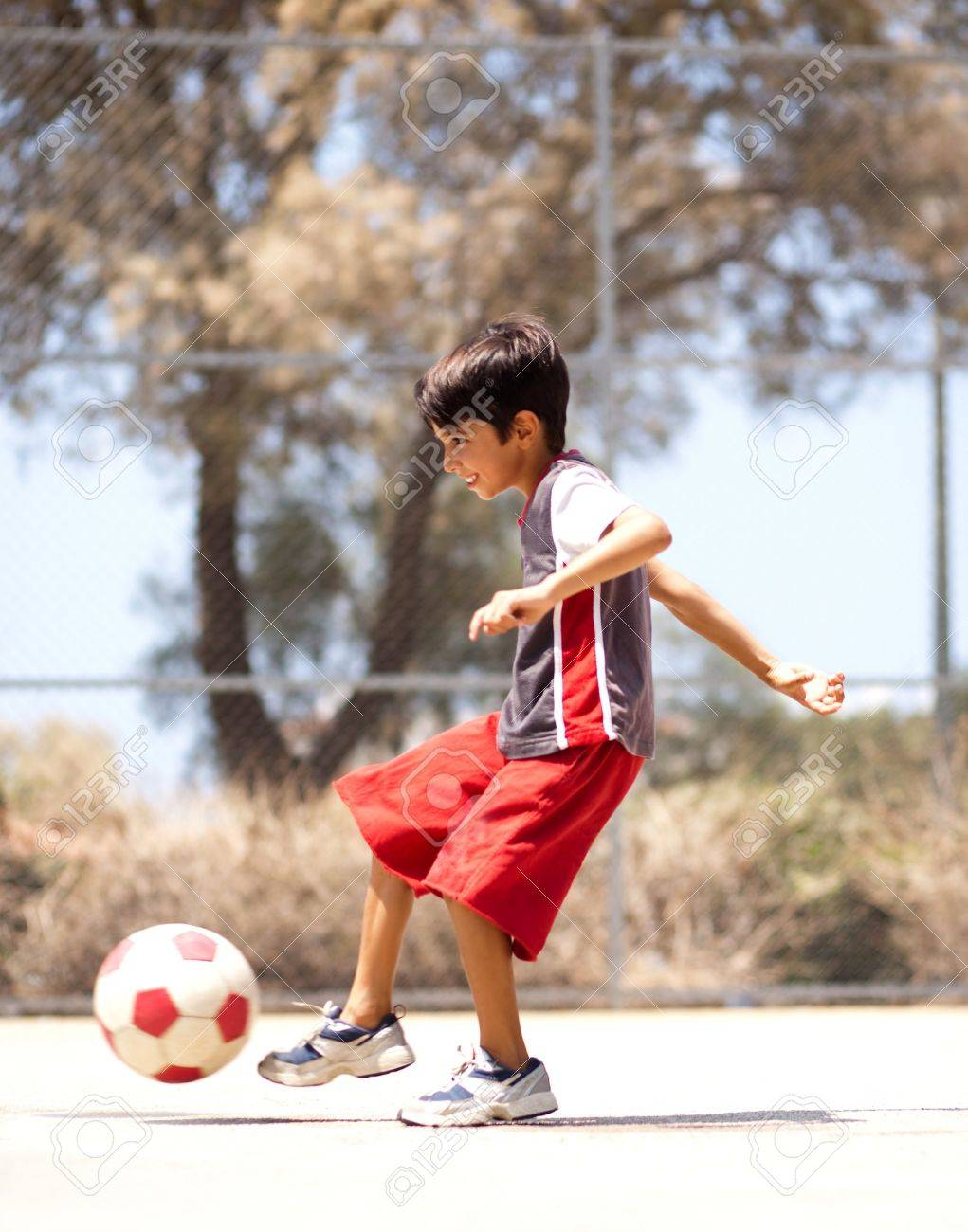 Young kid in action enjoying soccer, outdoors - 9795952