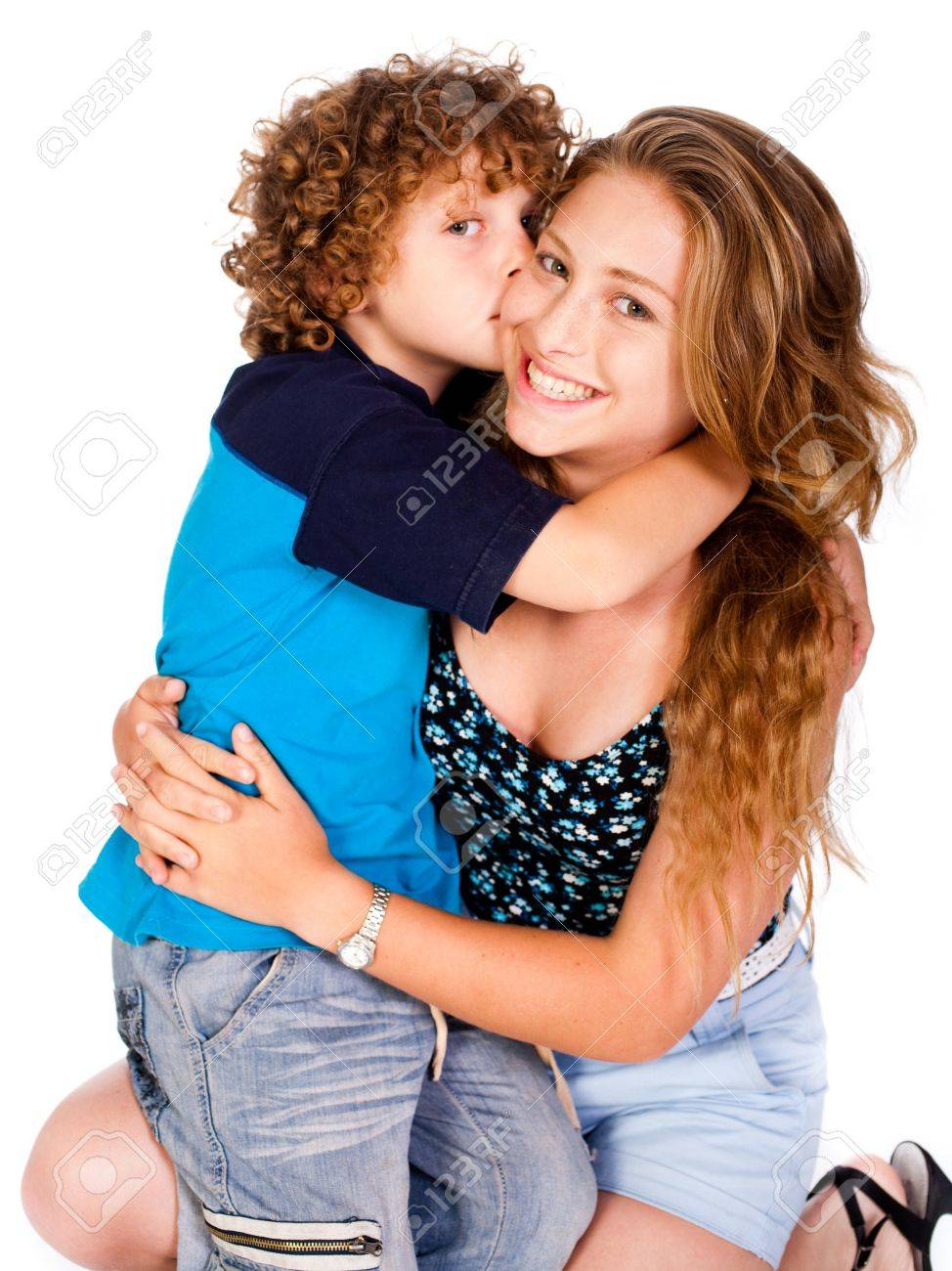 Young kid kissing his mom and looking at camera, isolated on white.. - 9796462
