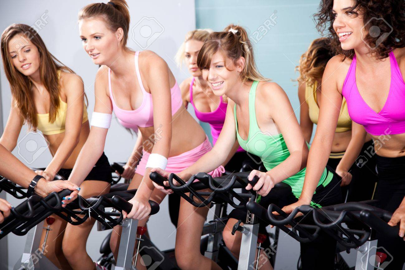 Four people on bicycles in a gym or fitness club for a workout. - 10473987