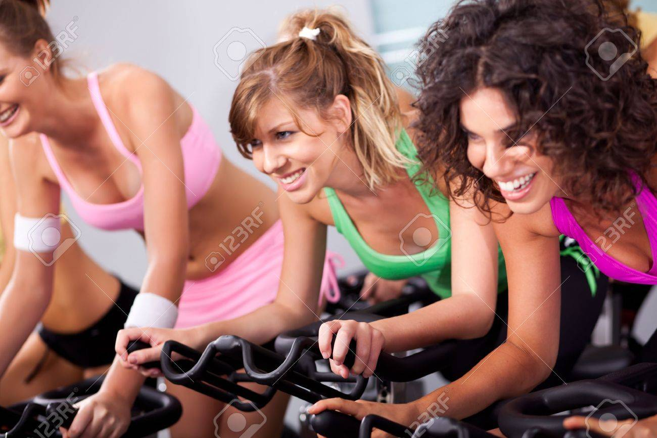 Gorgeous young females cycling in spinning class in gym. - 10473683