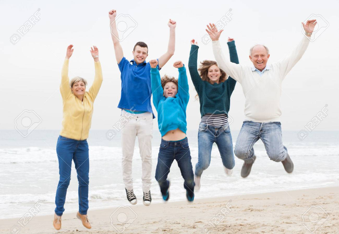 Happy family jumping on the air at beach - 26611340