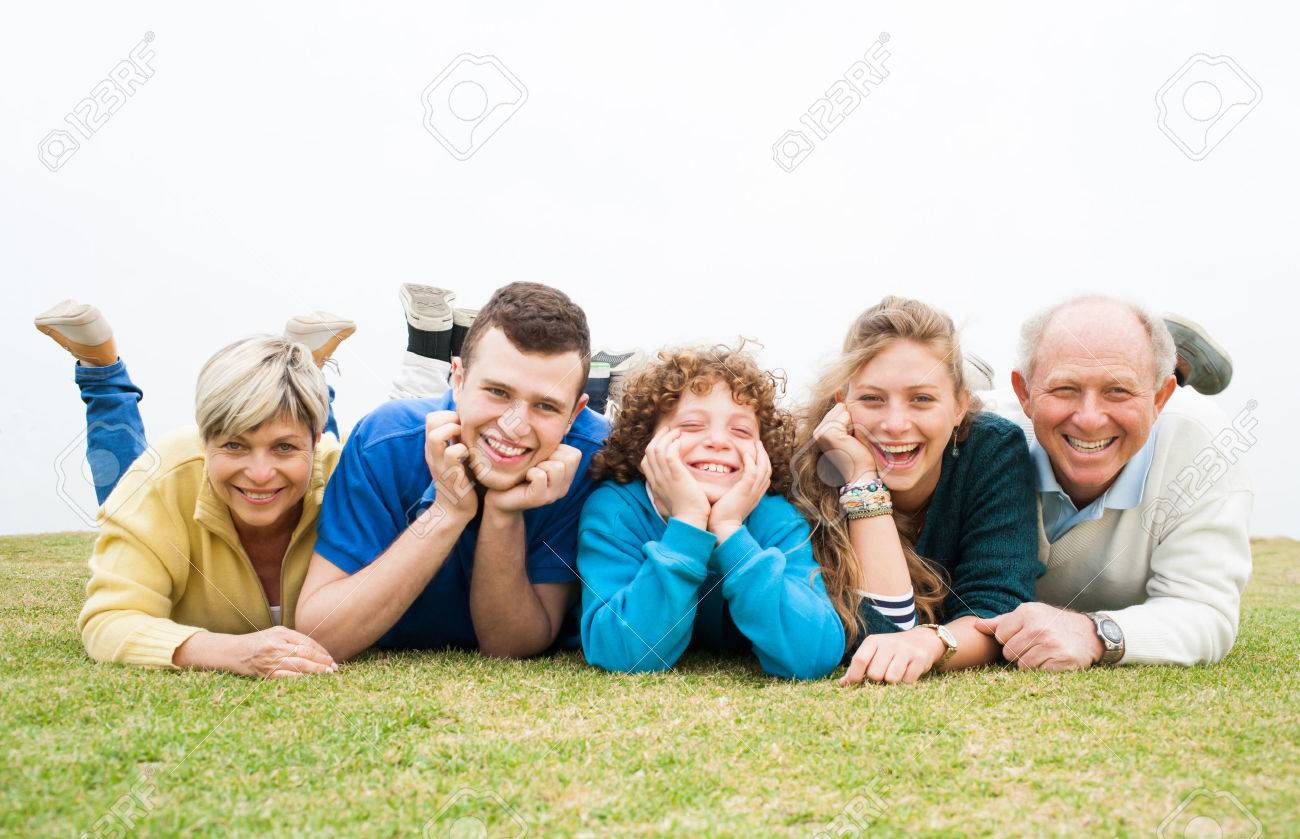 Excited happy family lying down on the grass - 26611485
