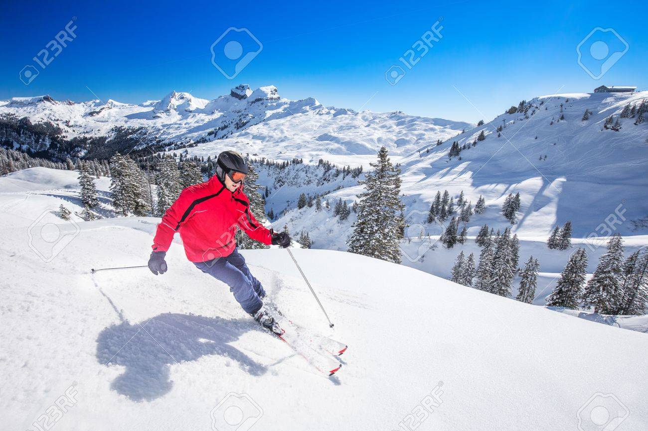 young man skiing in the hoch-ybrig ski resort in swiss alps,.. stock