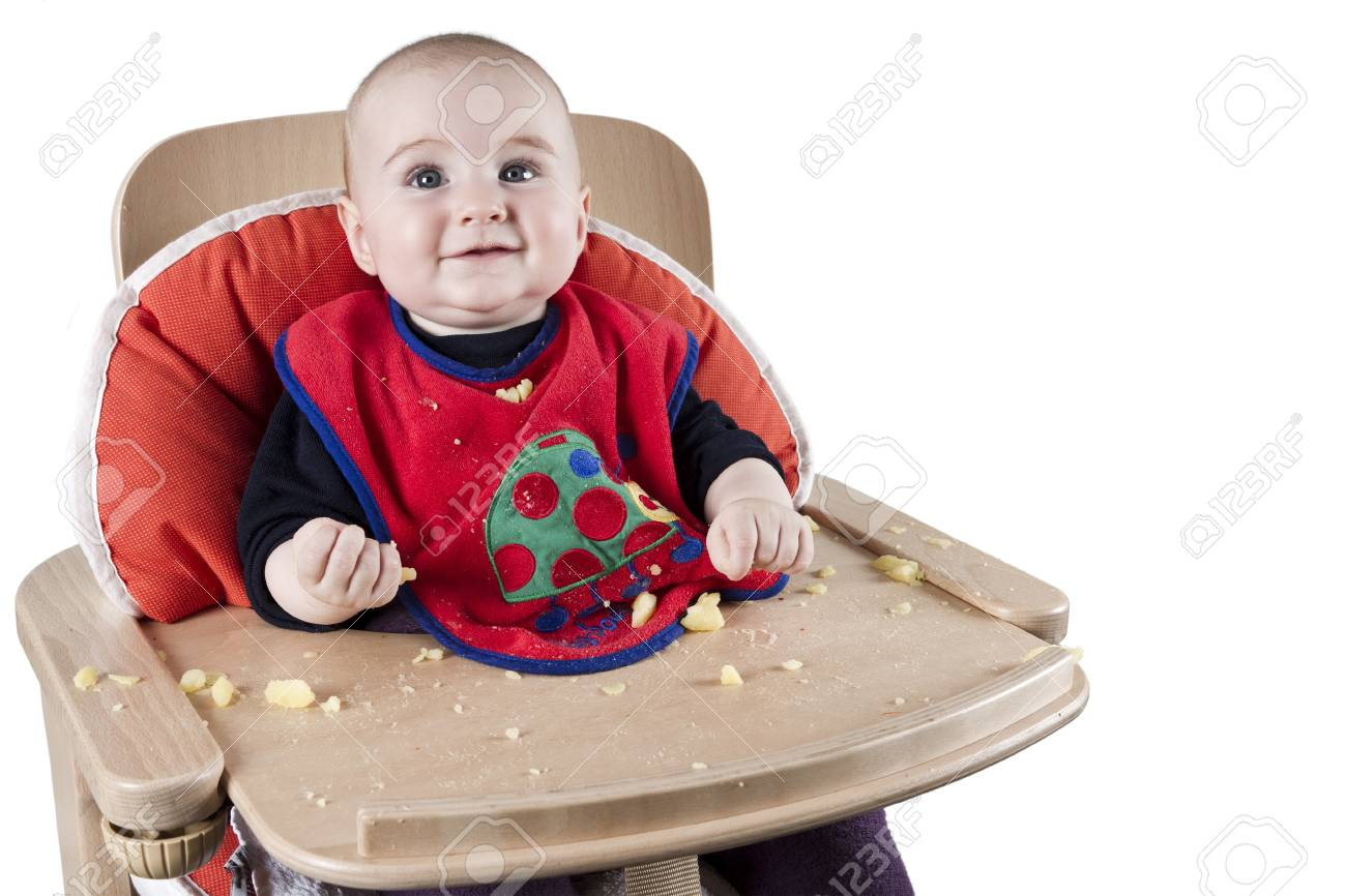 toddler eating potatoes in highchair Stock Photo - 12183230