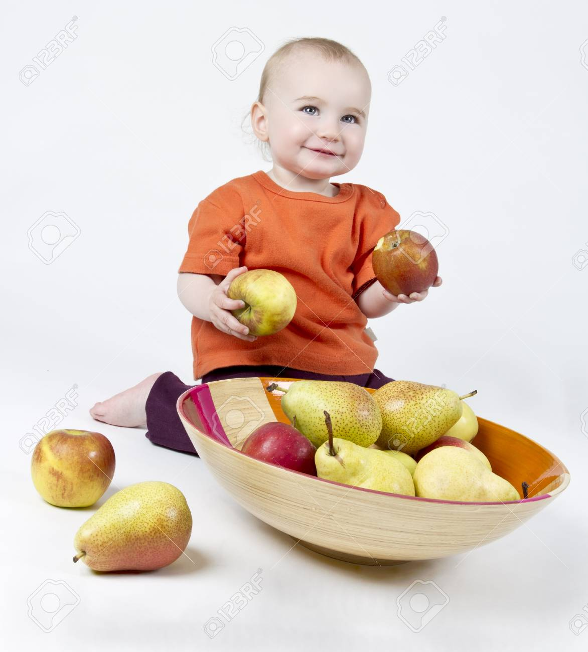 baby with apples and pears laying in bowl - studio shot Stock Photo - 13976449