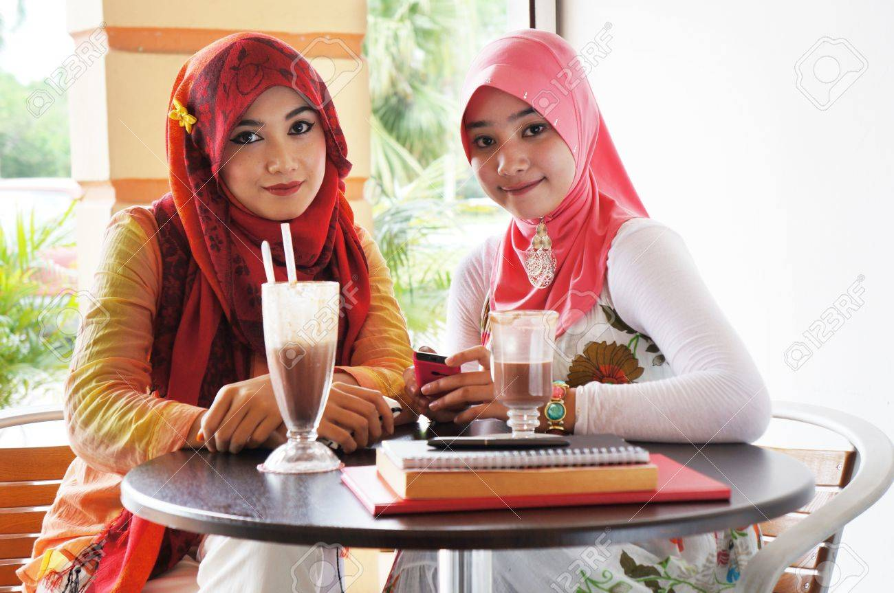 Two young stylish muslim women have a meet up at a cafe Stock Photo - 12408456