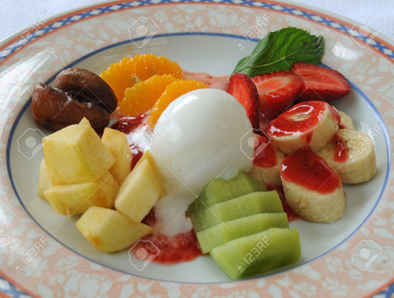 16018353-Les-fruits-frais-sont-r-partis-compl-t-avec-de-la-glace-Le-dessert-est-situ-sur-la-plaque-de-vacance-Banque-d'images