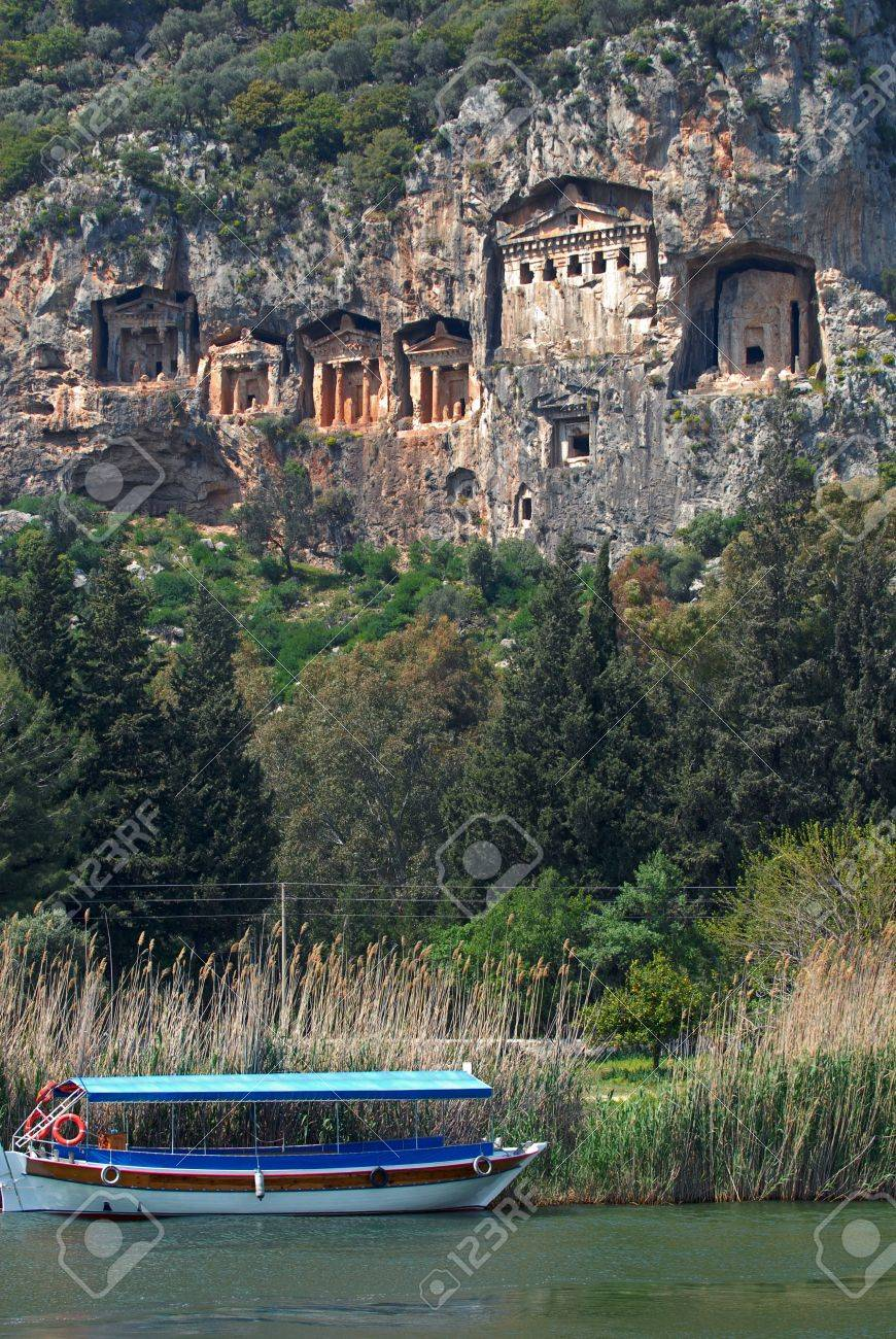 Necropolis of Lycian rock-cut tombs in the form of temple fronts carved into the vertical faces of cliffs in the Dalyan river valley, Turkey  Tourist boat moored near waterside Stock Photo - 16017966