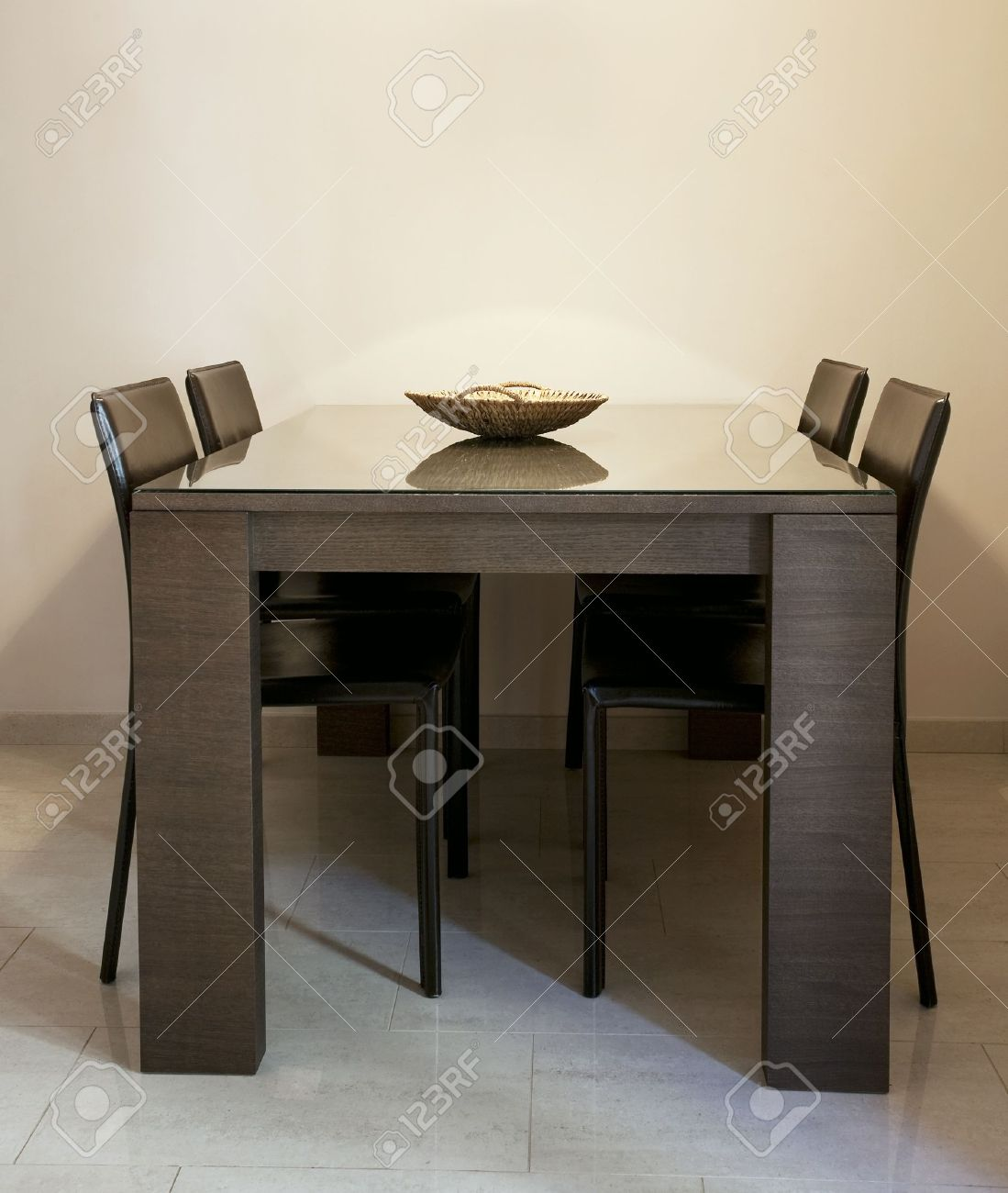 Moderno comedor con sillas marrón y una tabla con revestimiento de vidrio