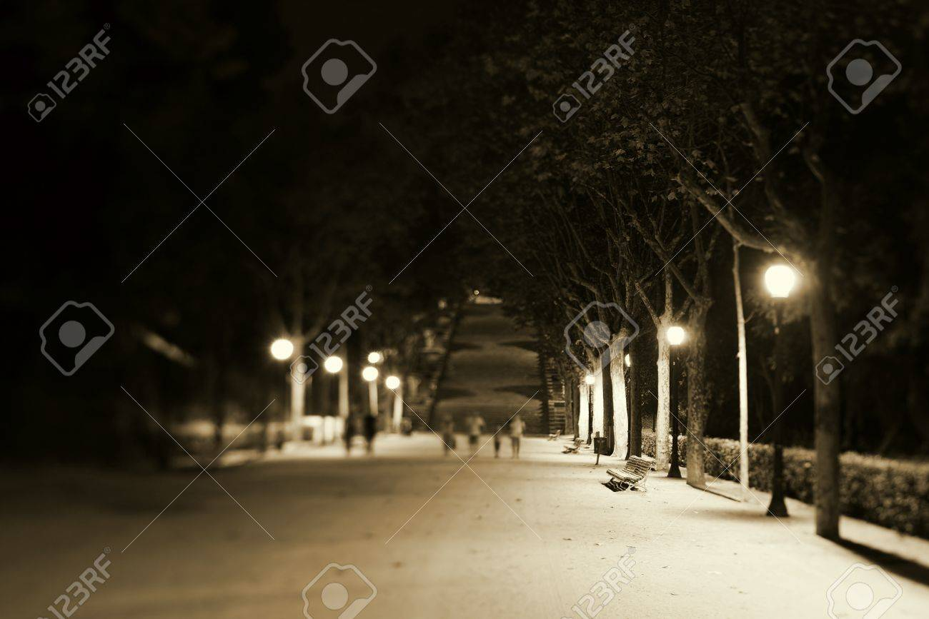 Nightscene with an illuminated park bench and walkway with distant pedestrians Stock Photo - 11230388