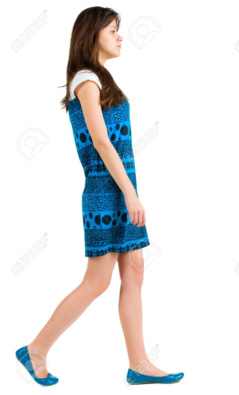 back side view of going young brunette girl . beautiful woman in blue dress in motion. backside view of person. Isolated over white background. Rear view people collection. - 13355675