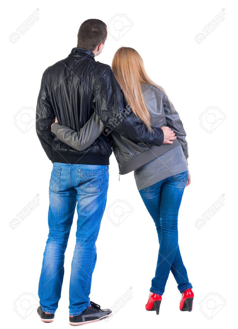 Back view of young couple (man and woman) hug and look into the distance. beautiful friendly girl and guy in jacket and jeans together. Rear view. Isolated over white background. Stock Photo - 13773011