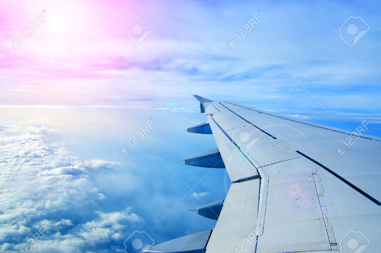 wing of an airplane flying above the clouds people look at the