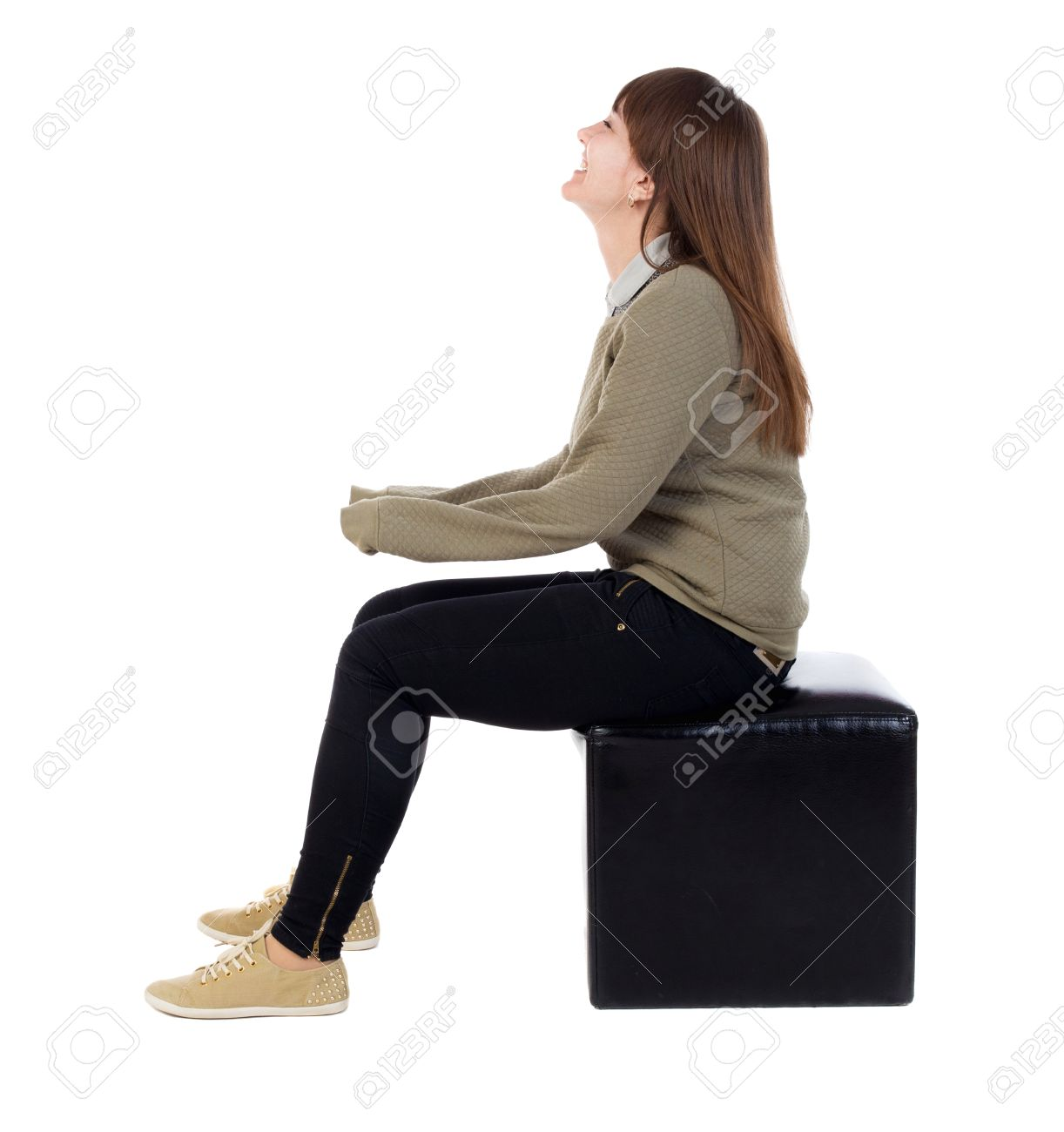 back view of young beautiful woman sitting. girl watching. Rear view people collection. backside view of person. Isolated over white background. The girl is sitting on a leather ottoman and smiling. - 51617278