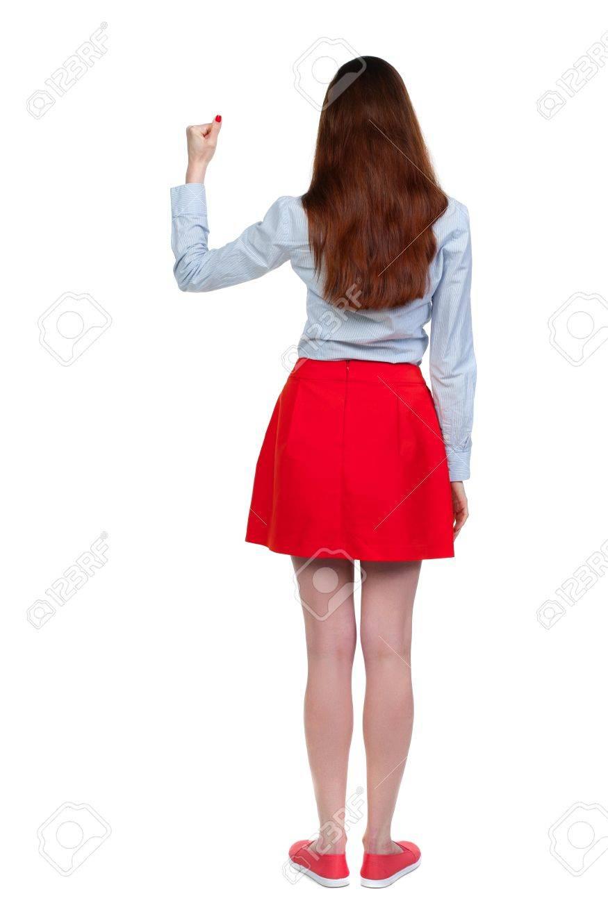 f3e8cd43e Vista posterior de la mujer. Levantado su puño en señal de Victoria Morena  de pelo largo en falda roja muestra el gesto de la victoria.