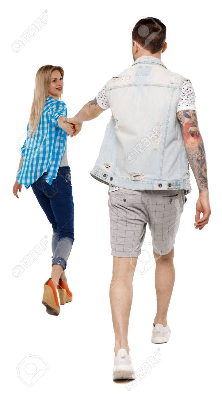 Back view of going couple. walking friendly girl and guy holding hands. Rear view people collection. backside view of person. Isolated over white background. Happy girl pulls the hand of her boyfriend. - 121742394