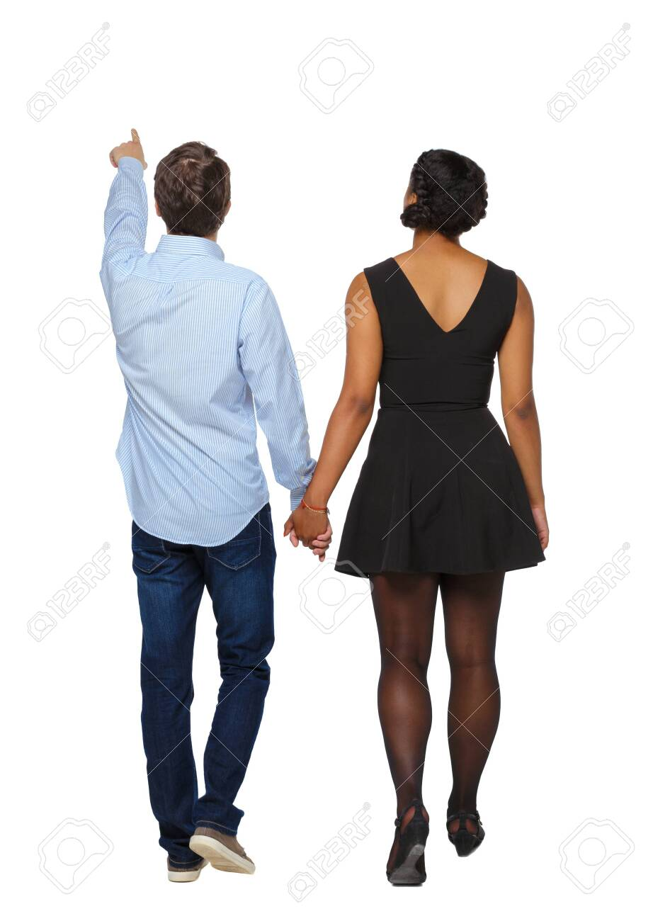 Back view of interracial going couple who points somewhere. walking friendly girl and guy holding hands. Rear view people collection. backside view of person. Isolated over white background. The guy leads the black girl by the hand. - 123233039
