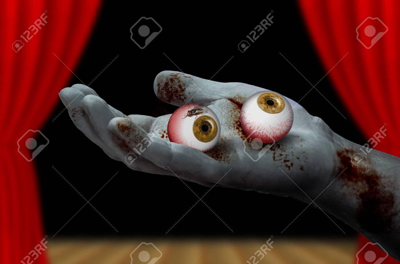 Zombie hand holding a pair of eyeballs - 141483485