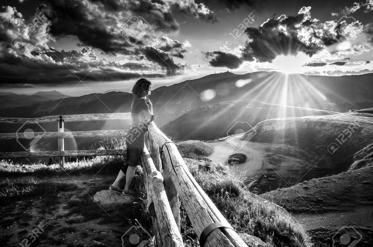 Black and white portrait of girl watching a beautiful sunset in a peaceful and tranquil place