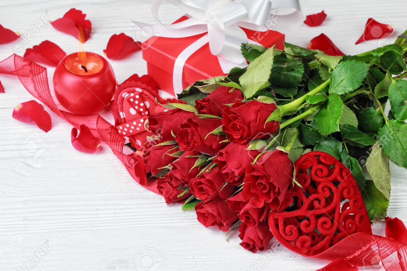 Valentines day background with a bouquet of beautiful red roses stock photo valentines day background with a bouquet of beautiful red roses gift box heart shaped ornaments and globe shaped candle on white wooden izmirmasajfo