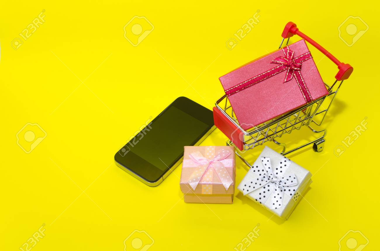 703fb11fd mini supermarket shopping cart with mini colorful gift box and smart phone  on yellow background