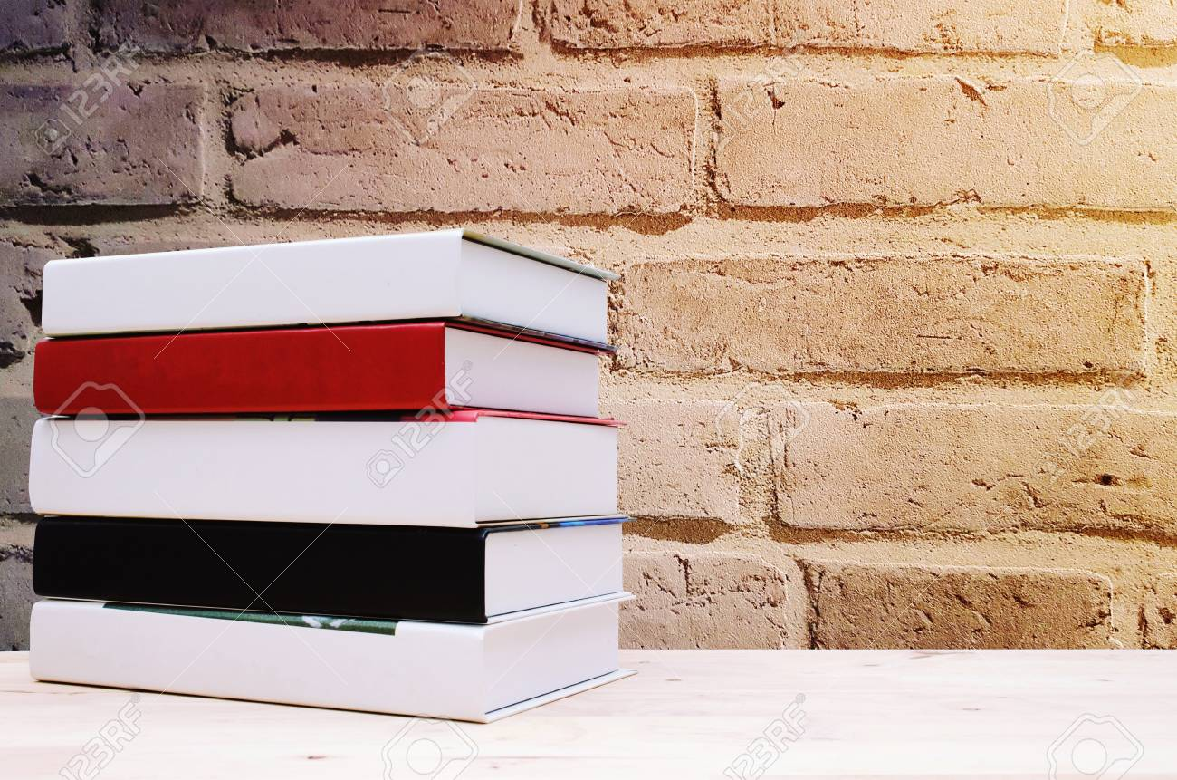 Stack Book On Desk No Labels Blank Spine With Brick Wall Background