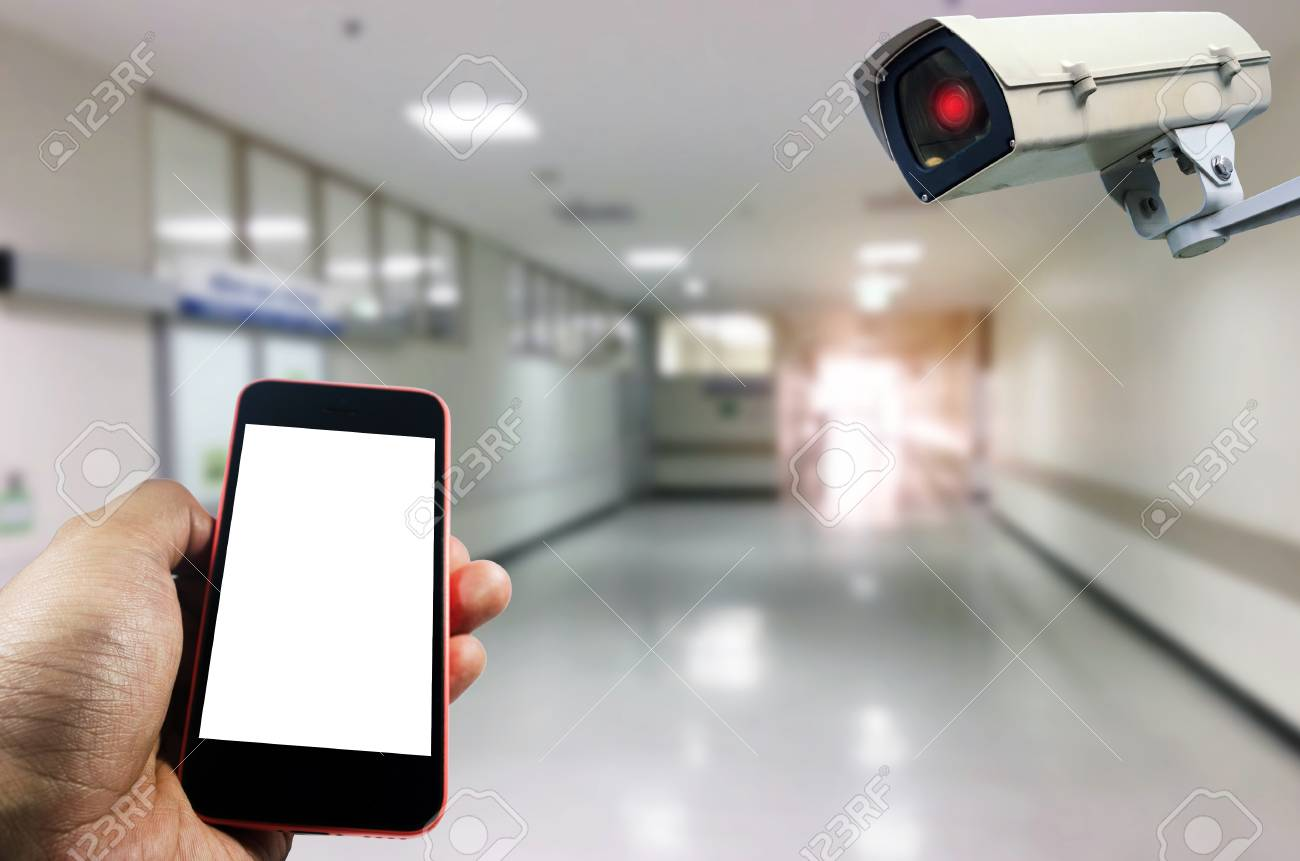 Hand Using Smart Phone Monitoring And CCTV Security Indoor Camera