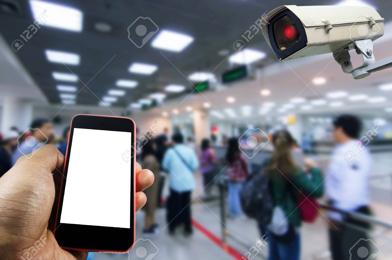 hand using mobile phone with blank screen and security camera