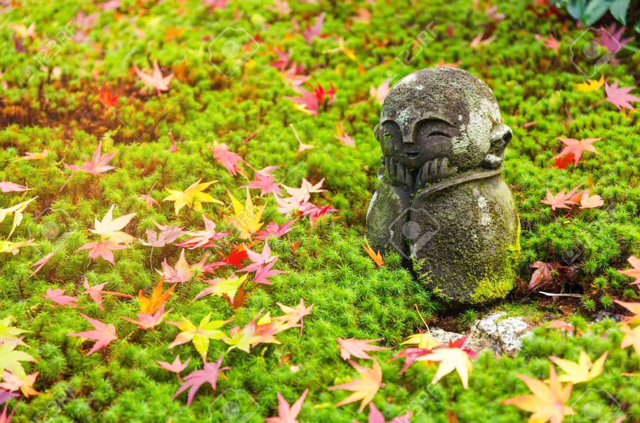 Stock Photo   Traditional Small Smiling Stone Statue Or Jizo Buddha Monk  Statue With Green Star Moss And Coloful Red Maple Leaves On Ground In A  Garden, ...