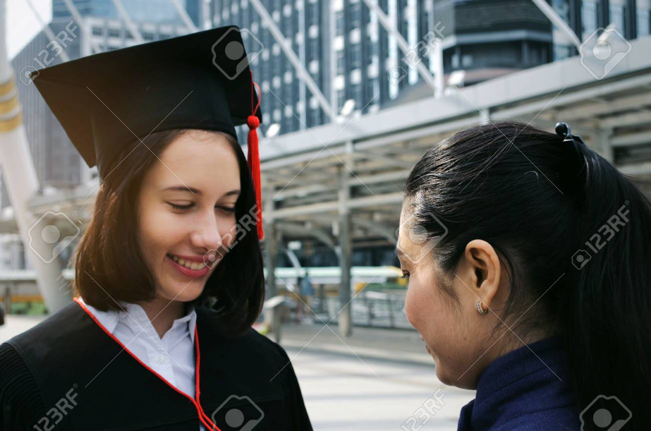 e393ef1fdab Stock Photo - You did it. happy asian mother congratulation graduation to  her caucasian daughter in city