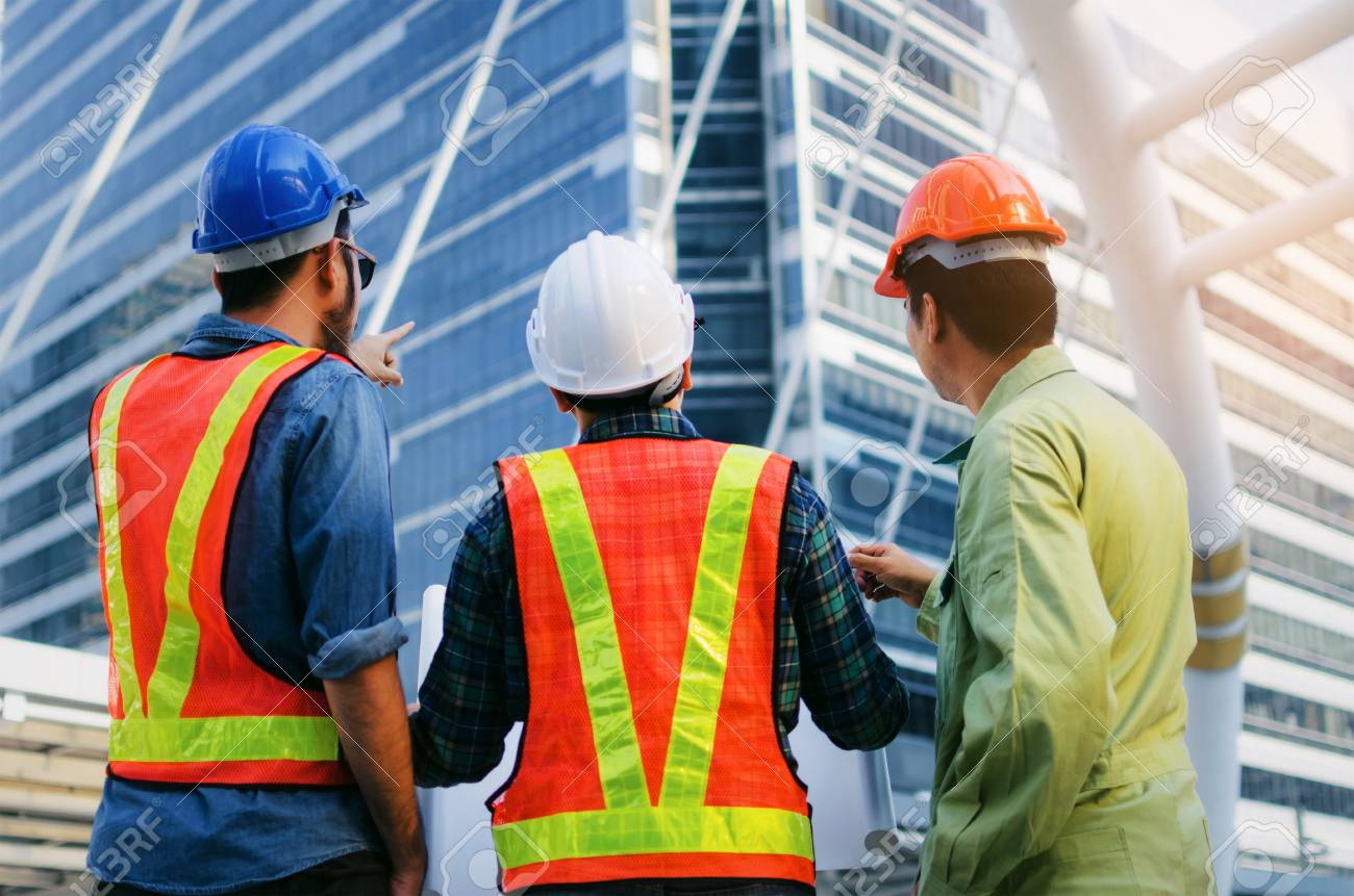 back view group of engineer technician and architect with safety helmet planning about building plan