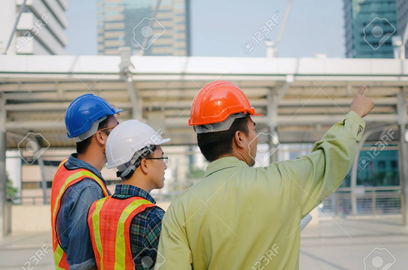 side view group of engineer technician and architect with safety helmet planning about building plan