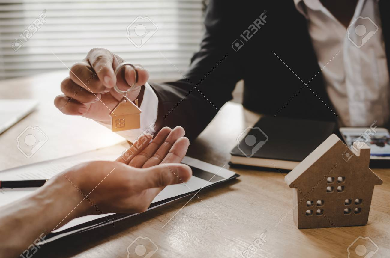 real estate broker manager giving house key to customer after signing contract for buying house in estate agent office, investment, home loan contract, buying house, real estate and insurance concept - 115429548