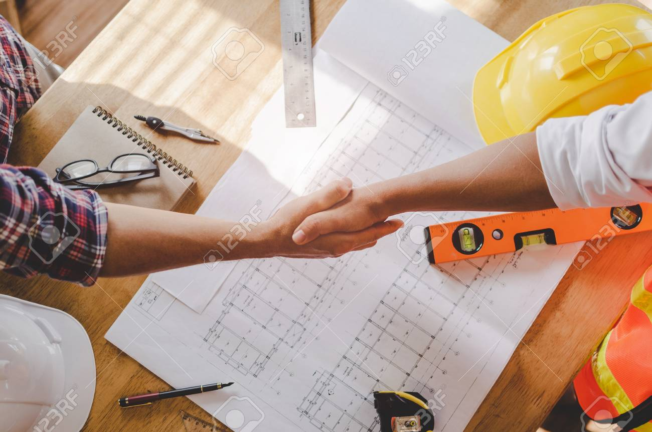 top view construction worker team contractor hand shake after finishing up business meeting to greeting start up project contract in construction site building, teamwork, partnership, industry concept - 117039570