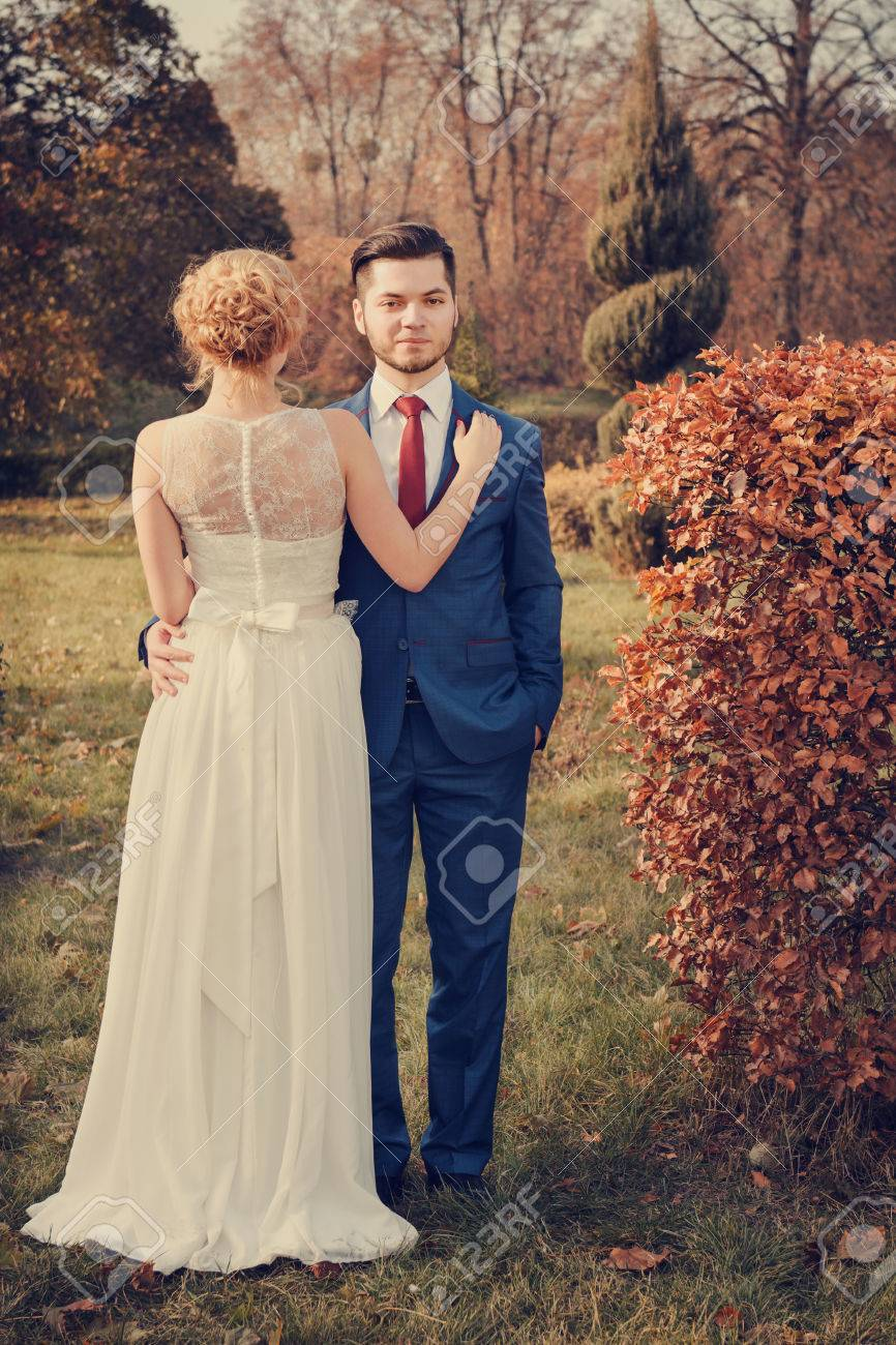 Stock photo vintage style of romantic wedding couple walking in park man looking at camera woman standing back to camera