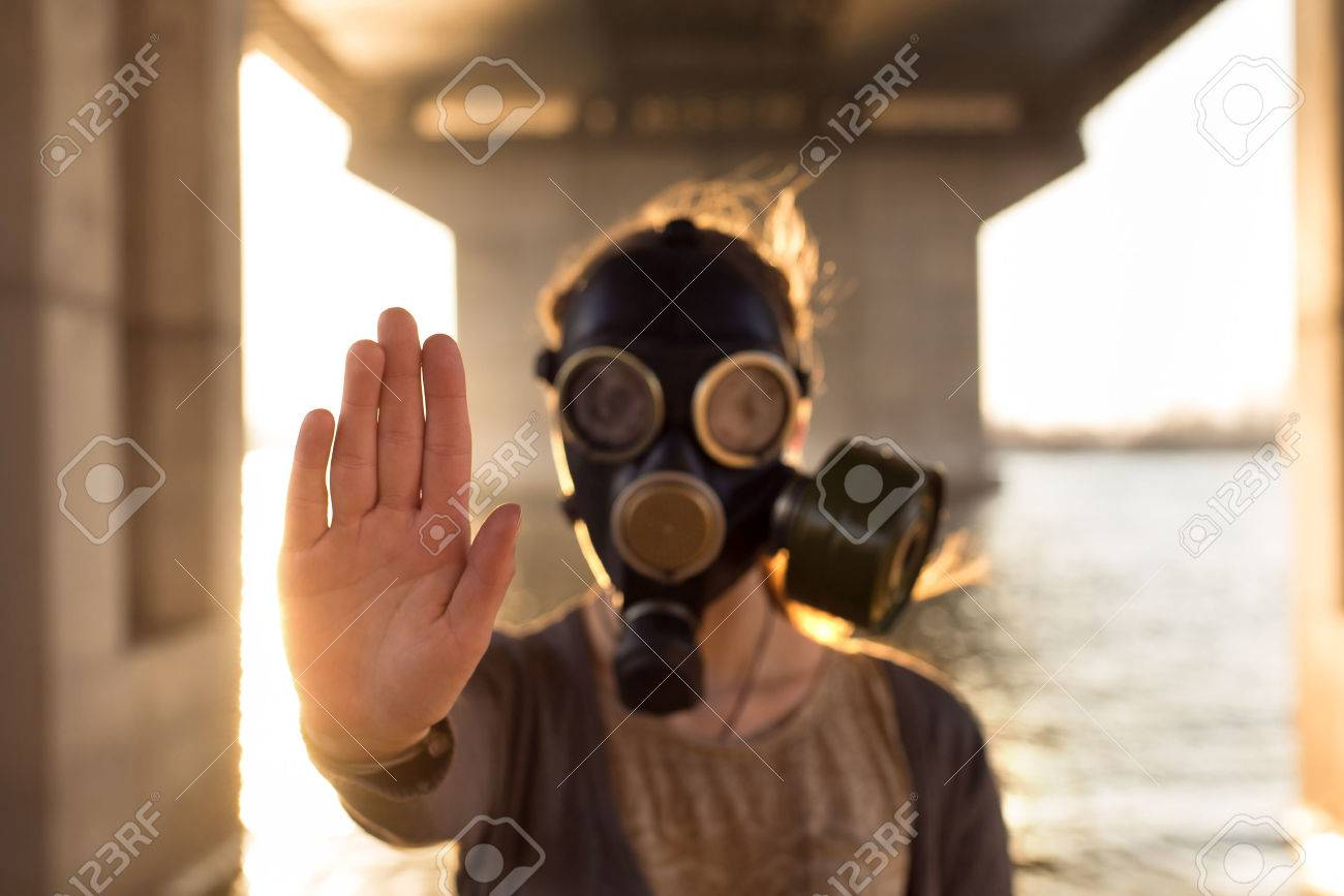 Ecological concept of air contamination. Woman in gas mask near water showing stop gesture - 41413018