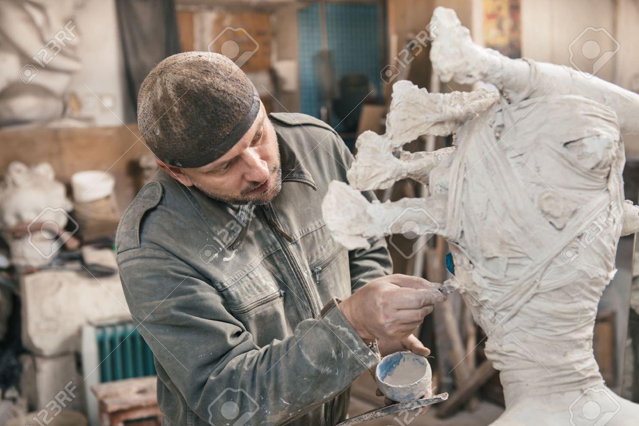 石膏と彼のワーク ショップで粘土からの彫刻家 сreating 彫刻 の写真 ...