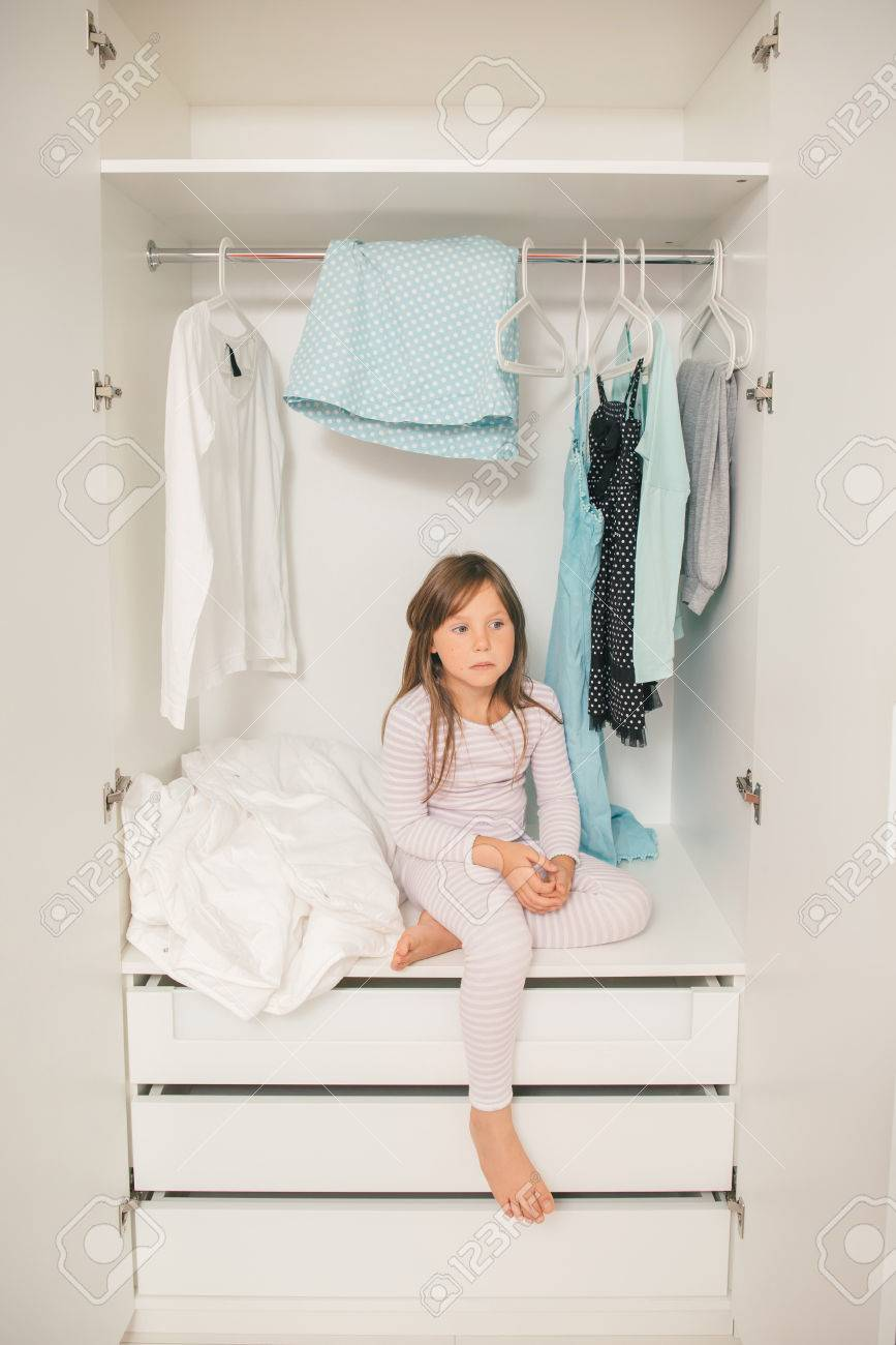 Alone Sad Little Girl Sitting In Motheru0027s Wardrobe. Concept: Problem To  Choose Clothes For