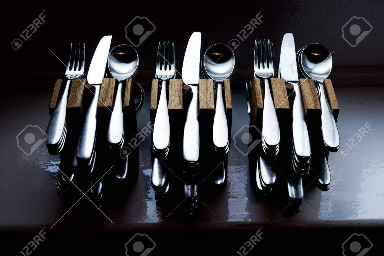 Twelve sets of beautifully lit quality cutlery, knives, forks,