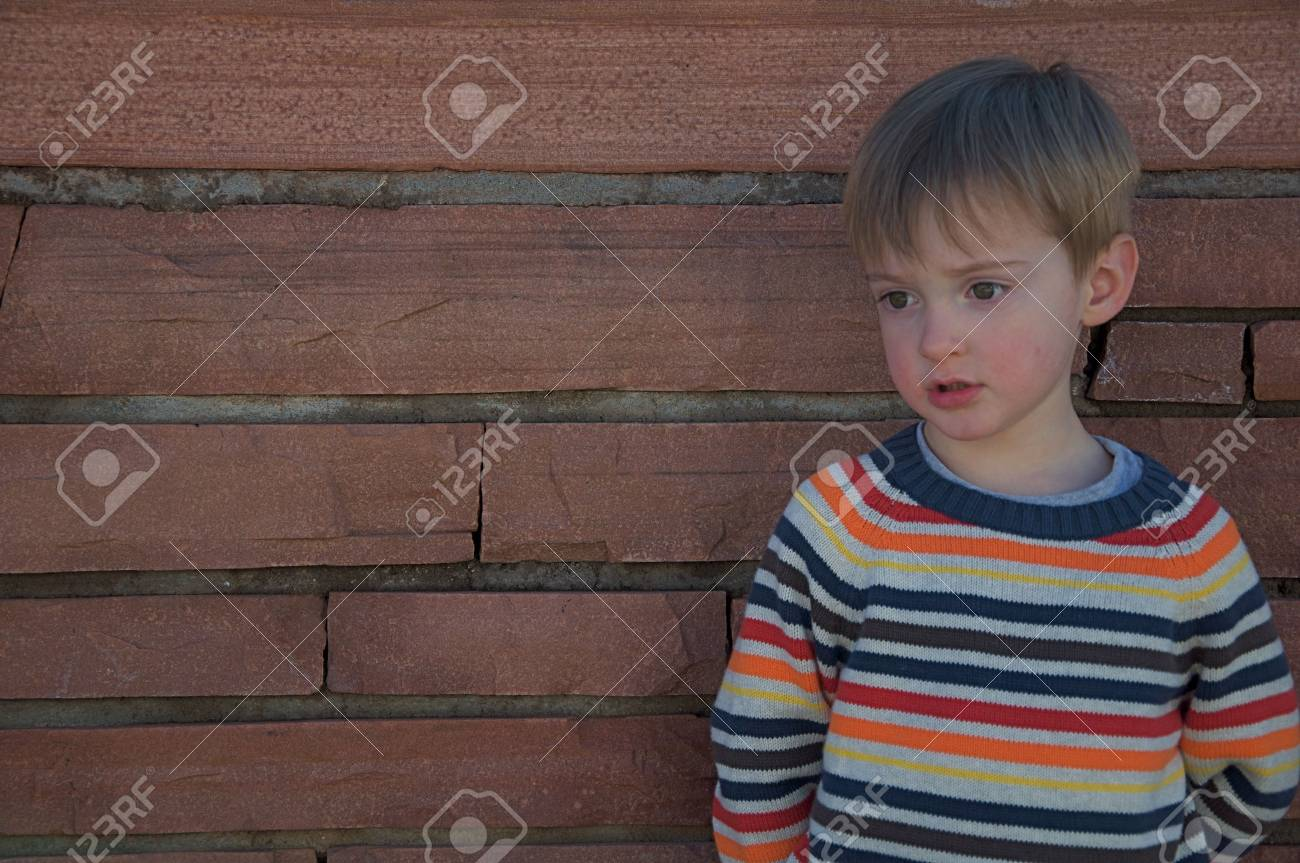 Little Boy Standing Against Stone Wall Stock Photo - 5830324