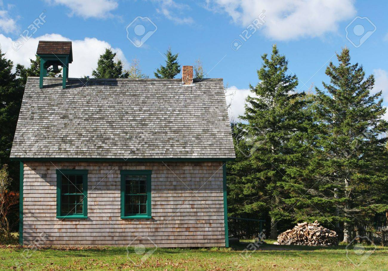 old fashioned school house with fire wood piled up outside stock